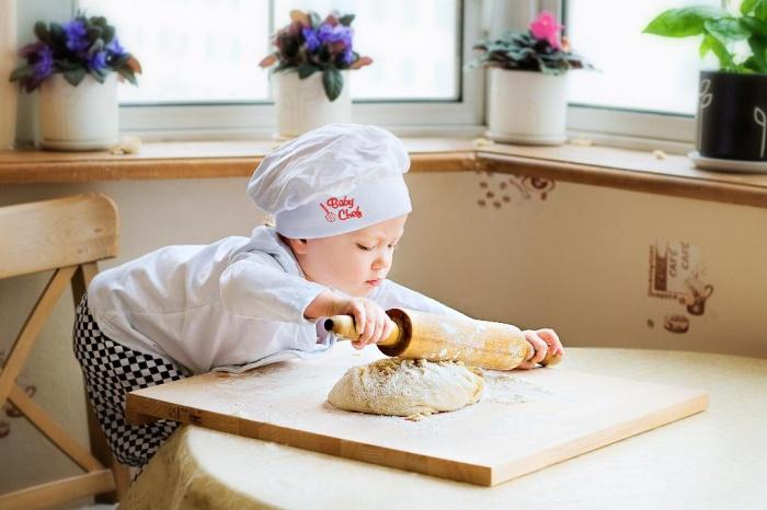 малыш раскатывает тесто